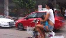 监拍女子边骑电动车边穿防晒衣 下一秒失控摔跤