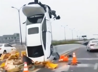 女司机将车垂直开上标志杆
