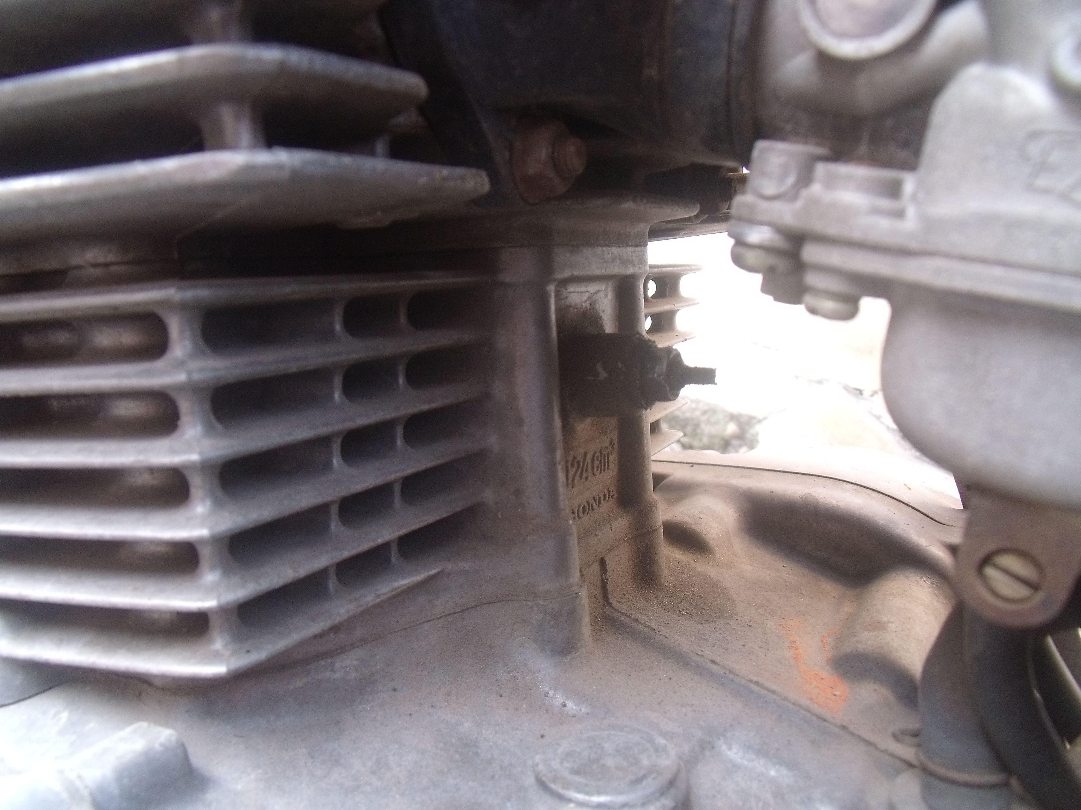 本田王摩托车发动机上面有一个可以调节的螺丝是做什么用的,图中间那图片