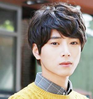 2,斜刘海的男生卷发发型,有点淡淡的棕色,搭配俊秀的脸庞,加上黄色的图片