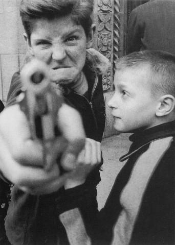 一张小孩子拿着玩具枪对着镜头的照片